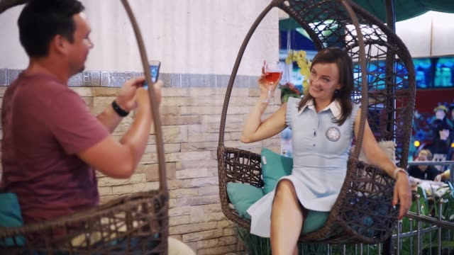 Romantic and love relationships. young couple on a date. A woman and a man are sitting on a swing. Male photographs female with a glass of wine, girl laughs