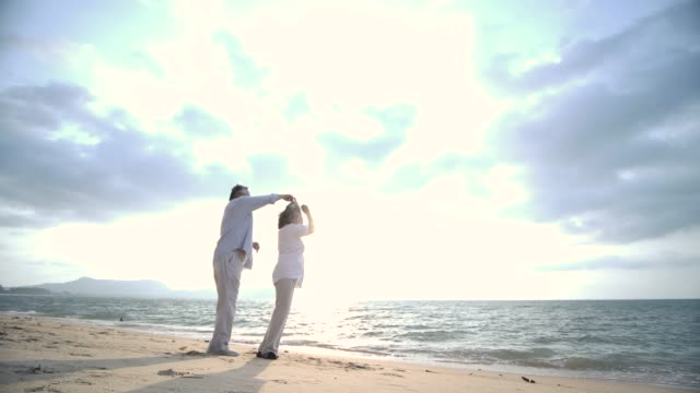 ロマンチックなアジア シニア カップルのスローモーションのビーチでダンスします。 ビデオ