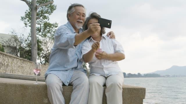ロマンチックなアジア シニア カップル夕日を見て、スローモーションで美しい熱帯のビーチでワインを楽しんでいます。 - 老夫婦点の映像素材/bロール