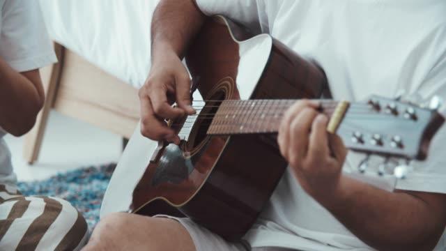 CU : Romantic asian senior man playing guitar for beautiful senior woman