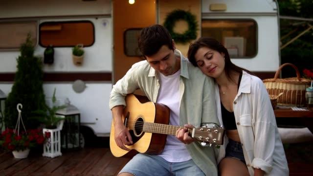 romantische, schöne paar sitzt im freien vor ihrem haus van und mann spielen die gitarre für freundin. outdoor. mädchen, das musik hört, sich auf seine schulter lehnt - menschliches gelenk stock-videos und b-roll-filmmaterial