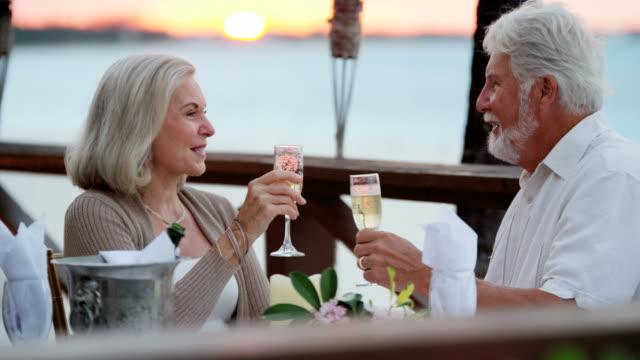 Romantic Caucasian senior couple enjoying evening beachfront dining
