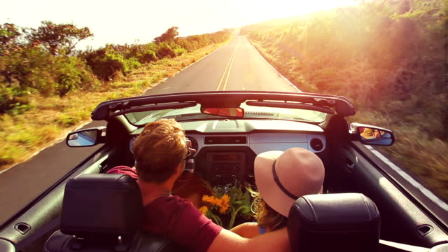 auto convertibile in tramonto romantico - vacanze video stock e b–roll