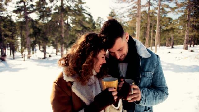 vídeos de stock, filmes e b-roll de romântico casal apaixonado, bebendo chocolate quente no bosque nevado - chocolate quente