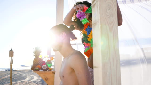 romantic couple in love Happy young woman makes surprise to her man putting lei garlands around his neck, Wind develops fabric of bungalow video