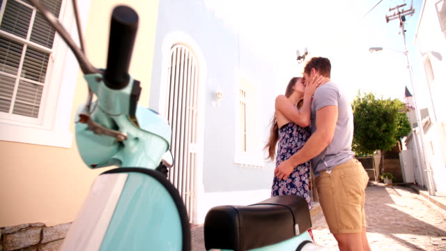 Romantic couple kissing in a street next to their scooter video