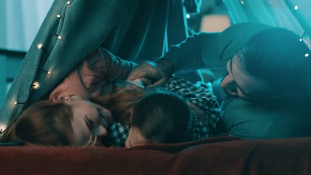 Romantic couple lying down at home tent and their daughter coming to them