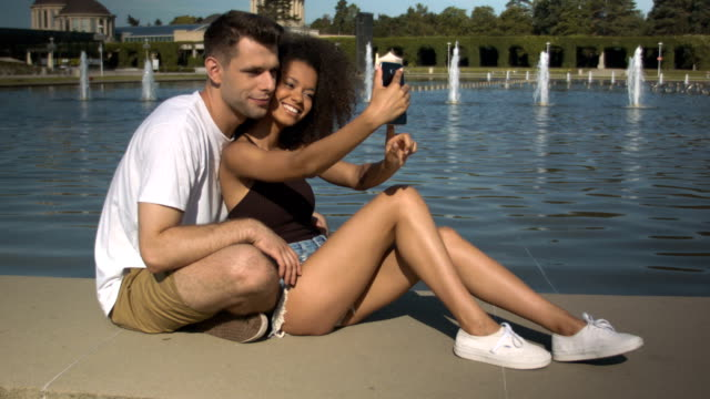 Romantic couple making photos by the lake in summer park. video