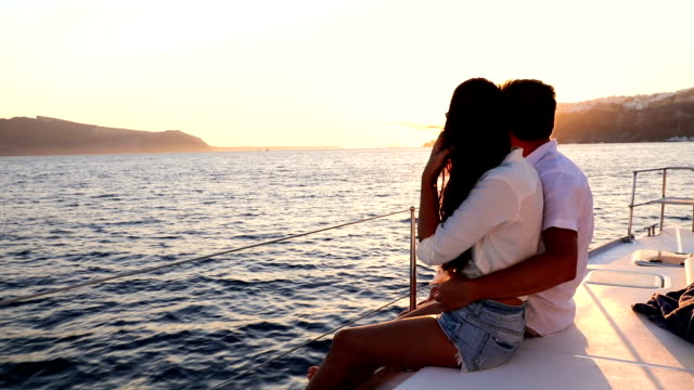 Romantic couple on yacht at sunset View of romantic couple on yacht at sunset greek islands stock videos & royalty-free footage