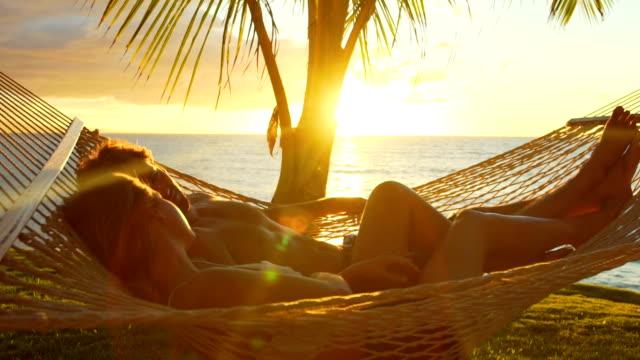 coppia romantica e rilassante in amaca tropicale al tramonto. estate vacanza di lusso. - amaca video stock e b–roll