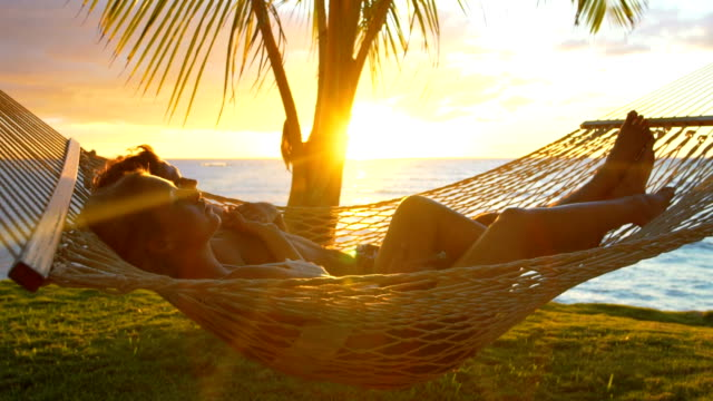 Romantic couple relaxing in tropical hammock at sunset. Summer Luxury Vacation. Romantic couple relaxing in tropical hammock at sunset. Summer Luxury Vacation. tourist resort stock videos & royalty-free footage