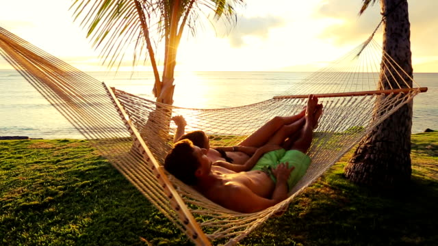 Romantic couple relaxing in tropical hammock at sunset video