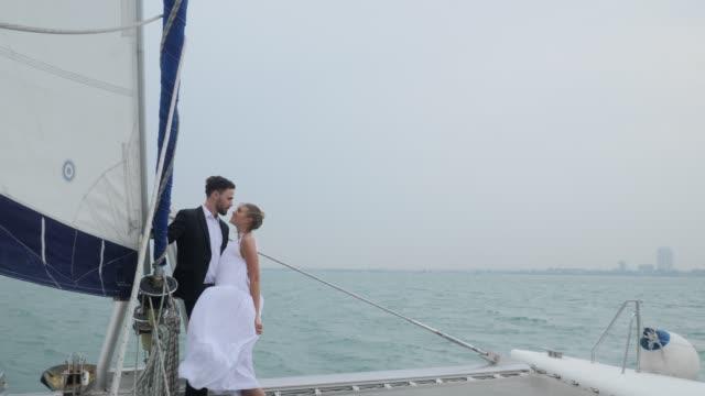 romantisk par segling, par är glada att fira på en segel båt, njuter av vacker dag segling begreppet kärlek - vin sommar fest bildbanksvideor och videomaterial från bakom kulisserna