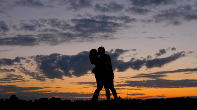 romantic couple silhouette. man with woman together are lovers kiss at sunset - valentines day stock videos and b-roll footage