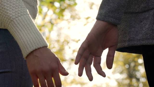 Romantic couple slowly grab hands after a small argument, symbol of reunion video