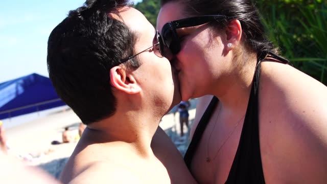 vídeos de stock, filmes e b-roll de romântico casal tomando uma selfie na praia - gordura