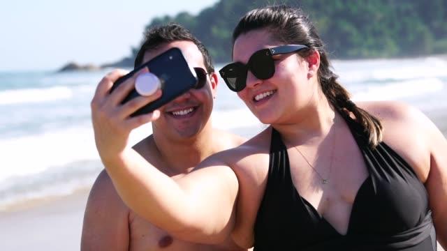 romantisches paar einnahme ein selfie am strand - übergrößen model stock-videos und b-roll-filmmaterial