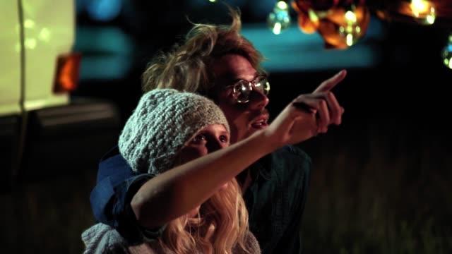 vídeos de stock e filmes b-roll de romantic couple talking while camping at night - europe points
