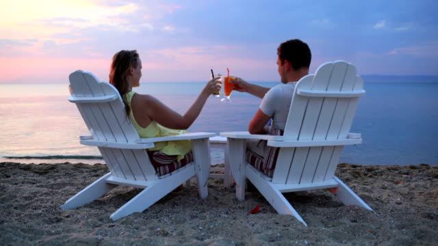 romantisches paar beim anstoßen den sonnenuntergang - tropischer cocktail stock-videos und b-roll-filmmaterial