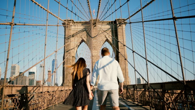 romantic couple walk along brooklyn bridge nyc, hold hands and kiss on a beautiful summer day, back view low angle 4k - city walking background video stock e b–roll