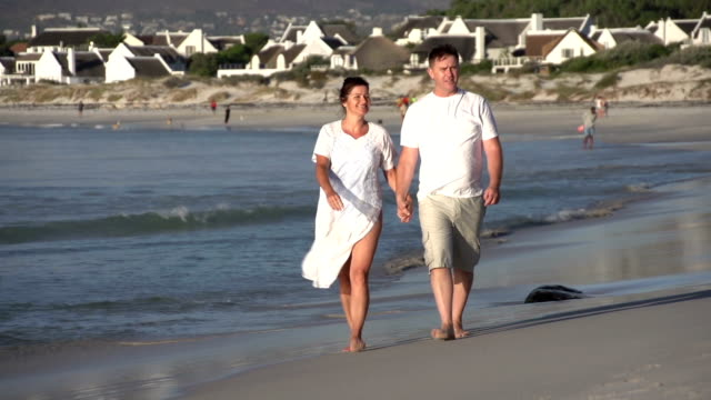 Romantic couple walking along beach, Cape Town, South Africa Man and woman enjoying a romantic walk along the beach, walking towards camera, Cape Town,South Africa newlywed stock videos & royalty-free footage