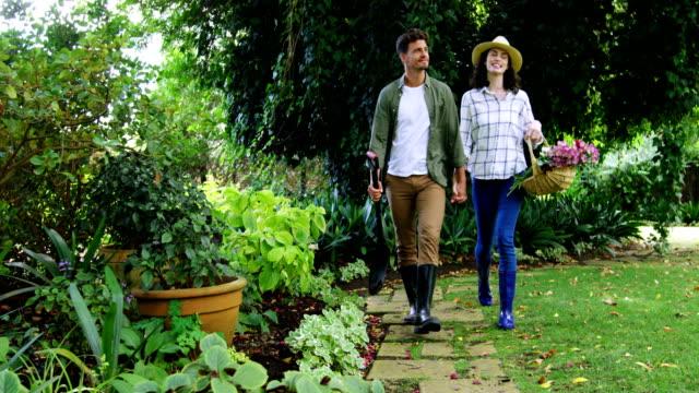 romantik çift el el parkta yürüyüş - bahçe ekipmanları stok videoları ve detay görüntü çekimi