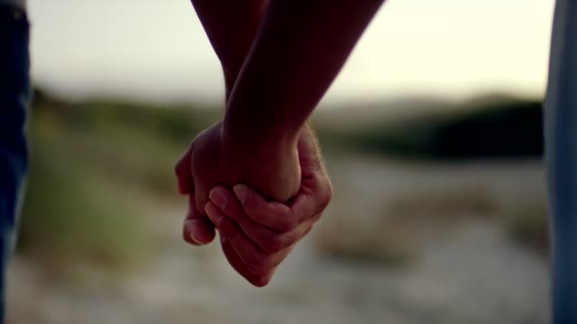 Romantic couple walking on the beach. Holding hands Summer holiday. Couple spending romantic evening at the beach falling in love stock videos & royalty-free footage