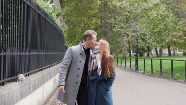 a romantic couple walking through a park together and kissing - true love angielski zwrot filmów i materiałów b-roll