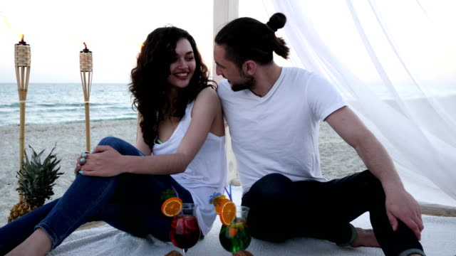 romantic couple with cocktails have fun in beach bungalow an exotic vacation, background tropical fruits, burning torches video