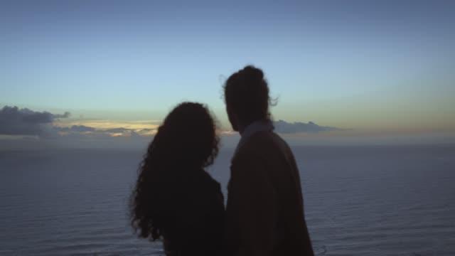 romantisches paar mit seekiuse im hintergrund - hinter stock-videos und b-roll-filmmaterial