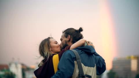 vidéos et rushes de rendez-vous romantique du jeune couple en plein centre-ville sur le coucher du soleil. heureux homme et femme câlin, bisou, appréciez le temps ensemble - jeune couple