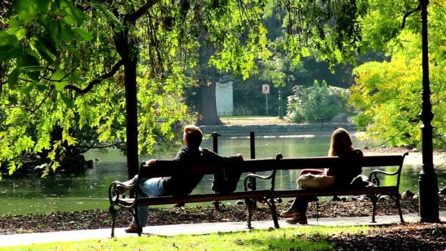 romantisk dating mannen och kvinnan separat på parkbänkar möte. vackra skott av europa, kultur och landskap. resor sightseeing, turist visningar sevärdheter i österrike. world travel, västra europeiska resa stadsbild, utomhus skott - vidbild bildbanksvideor och videomaterial från bakom kulisserna