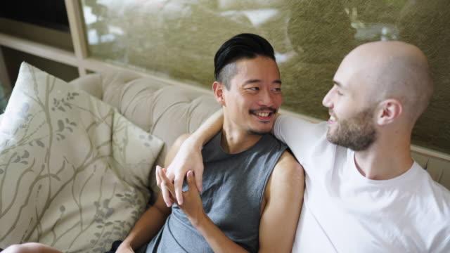 romantic gay couple embracing on sofa - telecomando background video stock e b–roll
