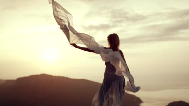 romantic girl in long dress enjoying the wind. standing on a cliff - seta video stock e b–roll