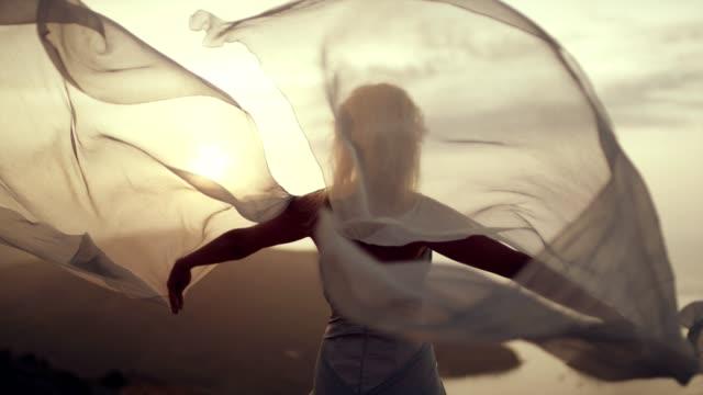 romantisk flicka i lång klänning njuter av vinden. står på en klippa - aftonklänning bildbanksvideor och videomaterial från bakom kulisserna