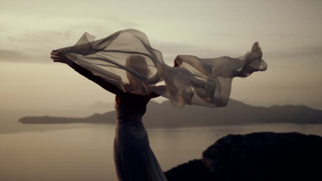 Romantic girl in long dress enjoying the wind. Standing on a cliff Young woman in long summer dress flying in the wind standing on a rocky shore dress stock videos & royalty-free footage