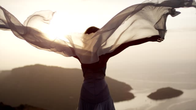 romantic girl in long dress enjoying the wind. standing on a cliff - красавица стоковые видео и кадры b-roll