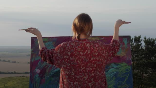 vidéos et rushes de image romantique de jeune artiste de fille qui peint dans la nature. la fille se tient près de l'image avec des brosses dans ses mains et les déplace. - toile à peindre
