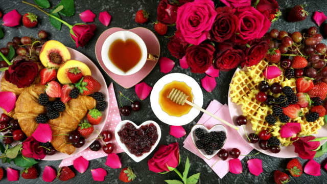 romantic indulgent breakfast with croissants, pancakes, waffles fruit and roses. - cucina francese video stock e b–roll