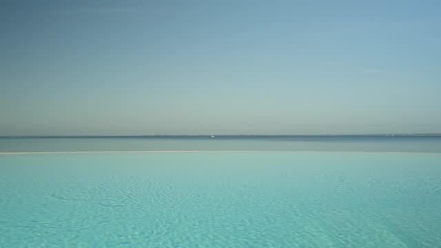 antenn, närbild: romantiska infinitypool med utsikt över vackra blå havet - på gränsen bildbanksvideor och videomaterial från bakom kulisserna