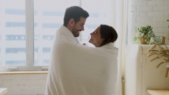 Romantic loving young couple warming covered with plaid in kitchen Romantic loving young couple warming covered with plaid in kitchen, happy affectionate husband embracing wife cuddling bonding laughing in cozy morning at home wrapped with blanket enjoy honeymoon blanket stock videos & royalty-free footage