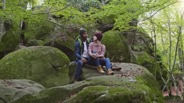 Romantic man and woman sitting on rock in forest