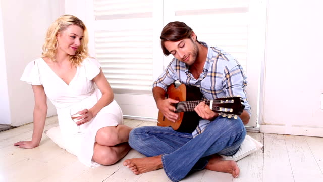 Romantic man playing guitar for his girlfriend Romantic man playing guitar for his girlfriend at home in the living room girlfriend stock videos & royalty-free footage