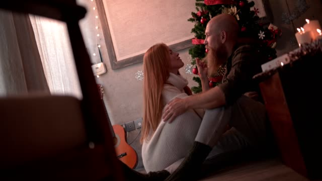Romantic mature couple under Christmas tree relaxing on Christmas day video