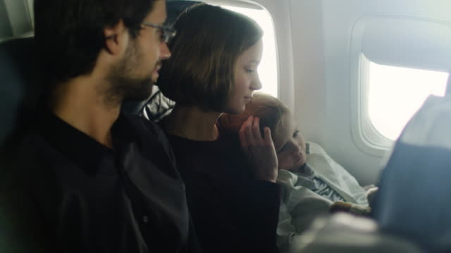 Romantic moment with a family with child on board of a plane next to a window. video