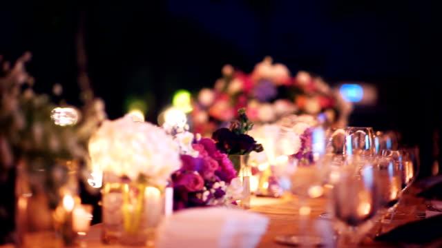vídeos de stock e filmes b-roll de slo mo romantic outdoor wedding table with flower arrangement and candles. - muita comida