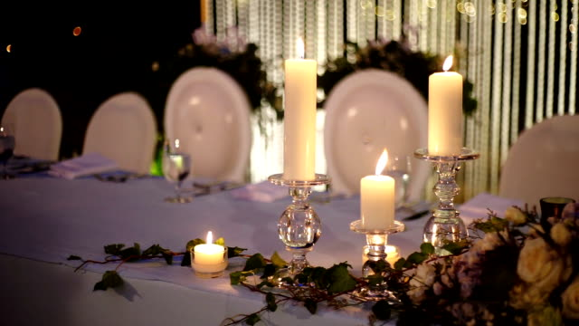 Romantic outdoor wedding table with fresh flowers and candles on the table with blurred background.