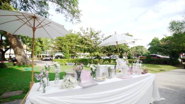 Romantic outdoor wedding table with fresh flowers in a vase on the table outdoors.