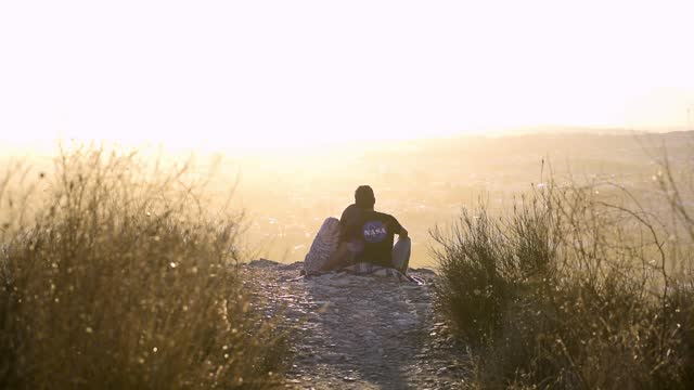 Romantic scene of a couple watching the sunset in mountain. Loving couple dating in romantic scene outdoors.