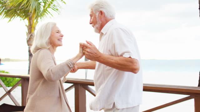 Romantic senior Caucasian couple dancing on hotel decking